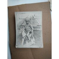 Фото девочки на игрушечной лошадке. 1950-е. 7х11 см