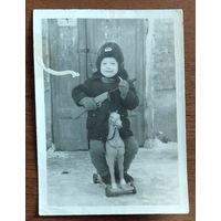 Фото мальчика с игрушечными лошадкой и автоматом. 8х11 см