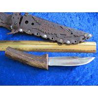 Нож ручной работы с выгнутой рукоятью из рога оленя с кожаным чехлом.
