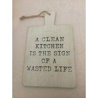 """Доска интерьерная на кухню например, дерево. Покупала в Германии, но так и не прижилась. Светлая, застаренная. Надпись: """"I clean kitchen is the sign of a wasted life"""". Размер 24 на 15 см."""